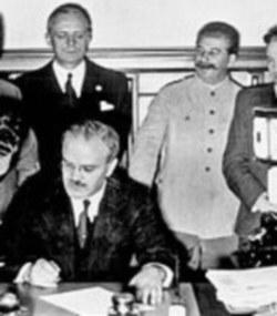 מולוטוב חותם על ההסכם, מאחוריו ריבנטרופ וסטאלין