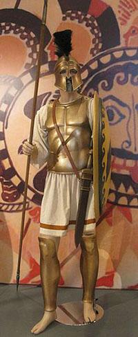 שיחזור של הופליט יווני, מגן ביד שמאל, חנית ארוכה (אחת!) ביד ימין וחרב על הירך. קסדה בעלת מיגון טוב על המצח (מתוך הוויקיפדיה)